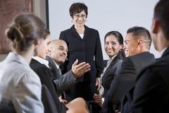 Empresarios diversos que conversan, mujer en el frente
