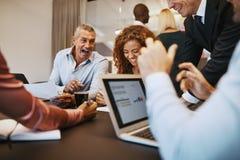 Empresarios diversos que ríen mientras que se encuentra junto en apagado imagen de archivo
