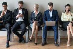 Empresarios diversos que se sientan en fila usando los teléfonos y el ordenador portátil de los dispositivos fotografía de archivo libre de regalías