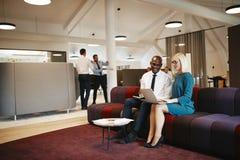 Empresarios diversos que trabajan junto en un sofá en una oficina foto de archivo