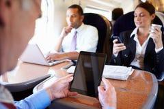 Empresarios en el tren usando los dispositivos de Digitaces Imagen de archivo