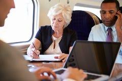 Empresarios en el tren usando los dispositivos de Digitaces Foto de archivo libre de regalías