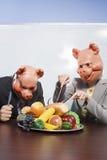 Empresarios en máscaras del cerdo con la comida plástica imagenes de archivo