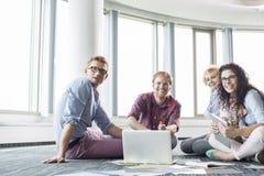 Empresarios felices que miran ausentes mientras que trabaja en piso la oficina creativa Fotografía de archivo libre de regalías
