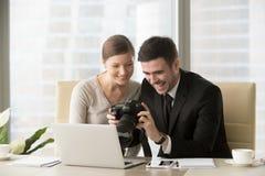 Empresarios felices que miran imágenes del tiroteo de foto en las RRPP Fotos de archivo