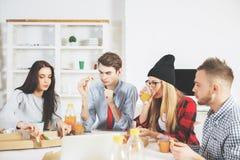Empresarios jovenes atractivos que comen en el lugar de trabajo Imagen de archivo