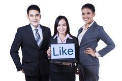 Empresarios jovenes que muestran como en el ordenador portátil Imagen de archivo libre de regalías