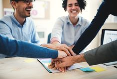 Empresarios jovenes que se sientan alrededor de la tabla en una oficina moderna, apilando las manos foto de archivo libre de regalías