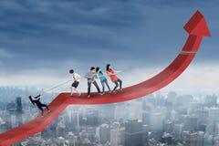 Empresarios jovenes que tiran del gráfico de beneficio Foto de archivo