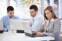 Empresarios jovenes que trabajan en sala de reunión Imagen de archivo