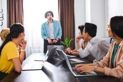 empresarios multiétnicos que se sientan en la tabla con los ordenadores portátiles durante el encuentro en moderno foto de archivo libre de regalías