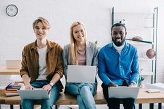 empresarios multiculturales sonrientes que usan los ordenadores portátiles y sentándose en la tabla en moderno foto de archivo