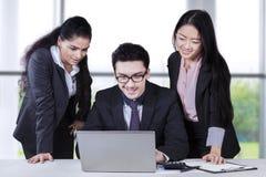 Empresarios multirraciales que usan el ordenador portátil foto de archivo libre de regalías