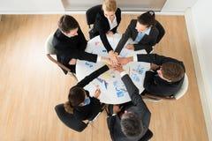 Empresarios que apilan las manos juntas imagenes de archivo