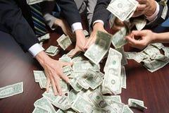 Empresarios que asen el dinero fotos de archivo