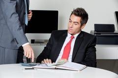 Empresarios que calculan finanzas imagen de archivo libre de regalías