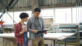 Empresarios que caminan en el taller de madera que habla sosteniendo la tableta e ir café almacen de metraje de vídeo