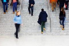 Empresarios que caminan encima de las escaleras, falta de definición de movimiento Imagen de archivo libre de regalías
