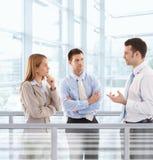 Empresarios que charlan en pasillo moderno de la oficina