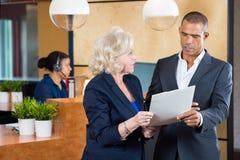 Empresarios que discuten en papeleo en la oficina Fotos de archivo
