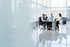 Empresarios que discuten junto en la sala de conferencias durante la reuni?n en la oficina imagen de archivo libre de regalías