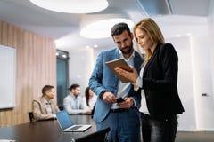 Empresarios que discuten mientras que usa la tableta digital en oficina imagenes de archivo