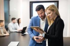 Empresarios que discuten mientras que usa la tableta digital en oficina foto de archivo