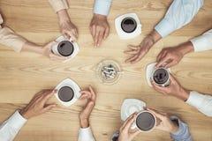 Empresarios que fuman en descanso para tomar café en el tablero de la mesa de madera Imagen de archivo