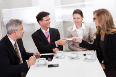 Empresarios que intercambian tarjetas sobre el café Foto de archivo libre de regalías