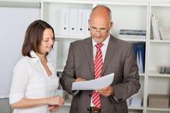 Empresarios que leen el documento en oficina Imágenes de archivo libres de regalías