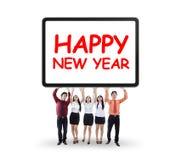 Empresarios que llevan a cabo el texto del Año Nuevo Fotos de archivo libres de regalías