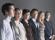 Empresarios que miran al hombre de negocios In Row Imagenes de archivo
