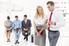 Empresarios que miran el fichero contra entrevista que espera de la gente para Foto de archivo libre de regalías