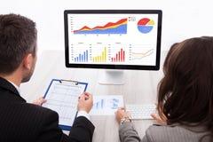 Empresarios que miran el gráfico en el ordenador Fotografía de archivo libre de regalías
