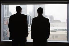 Empresarios que miran fuera de una ventana Imagen de archivo libre de regalías