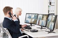 Empresarios que miran la cantidad múltiple de la cámara imagen de archivo