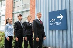 Empresarios que se colocan cerca de Job Center Signboard Foto de archivo libre de regalías