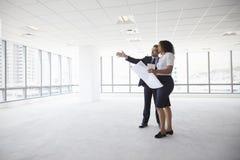 Empresarios que se encuentran para mirar planes en oficina vacía imagen de archivo