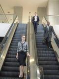 Empresarios que se mueven abajo en la escalera móvil en oficina Imagen de archivo libre de regalías