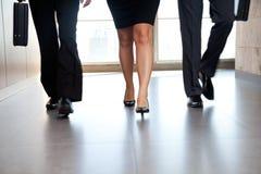 Empresarios que se mueven a lo largo del pasillo Foto de archivo