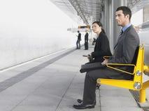 Empresarios que se sientan en banco de la estación de tren imagen de archivo libre de regalías