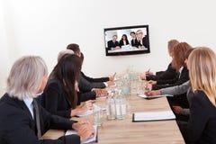 Empresarios que se sientan en la mesa de reuniones Imagen de archivo libre de regalías