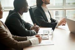 Empresarios que se sientan en la mesa de reuniones centrada en escuchar Foto de archivo libre de regalías