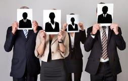 Empresarios que sostienen las fotografías en Front Of Faces Fotografía de archivo
