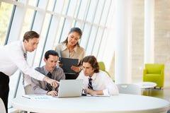 Empresarios que tienen reunión alrededor del vector en oficina moderna Imagenes de archivo