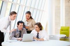 Empresarios que tienen reunión alrededor del vector en oficina moderna Foto de archivo libre de regalías