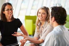 Empresarios que tienen reunión alrededor del vector en oficina moderna Foto de archivo