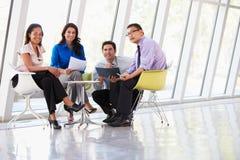 Empresarios que tienen reunión alrededor del vector en oficina moderna Imagen de archivo libre de regalías