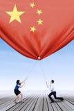 Empresarios que tiran abajo de una bandera china Imagen de archivo libre de regalías