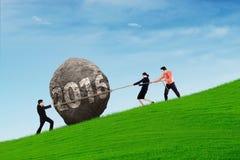 Empresarios que tiran de la piedra con los números 2016 Fotografía de archivo libre de regalías